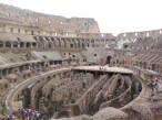 Inside the grand arena of the Colosseum. A portion you see exposed used be covered by a massive wood deck (partially recreated in the backdrop) over which the gladiators fought. Now the extensive tunnel and storage system located underneath the arena is exposed for all to view.